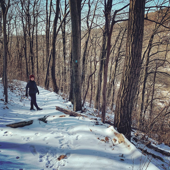 woman on snowy trail in woods